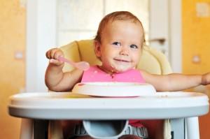 Lachende baby in kinderstoel met bordje pap